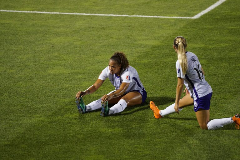 two women soccer players stretching legs on lawn